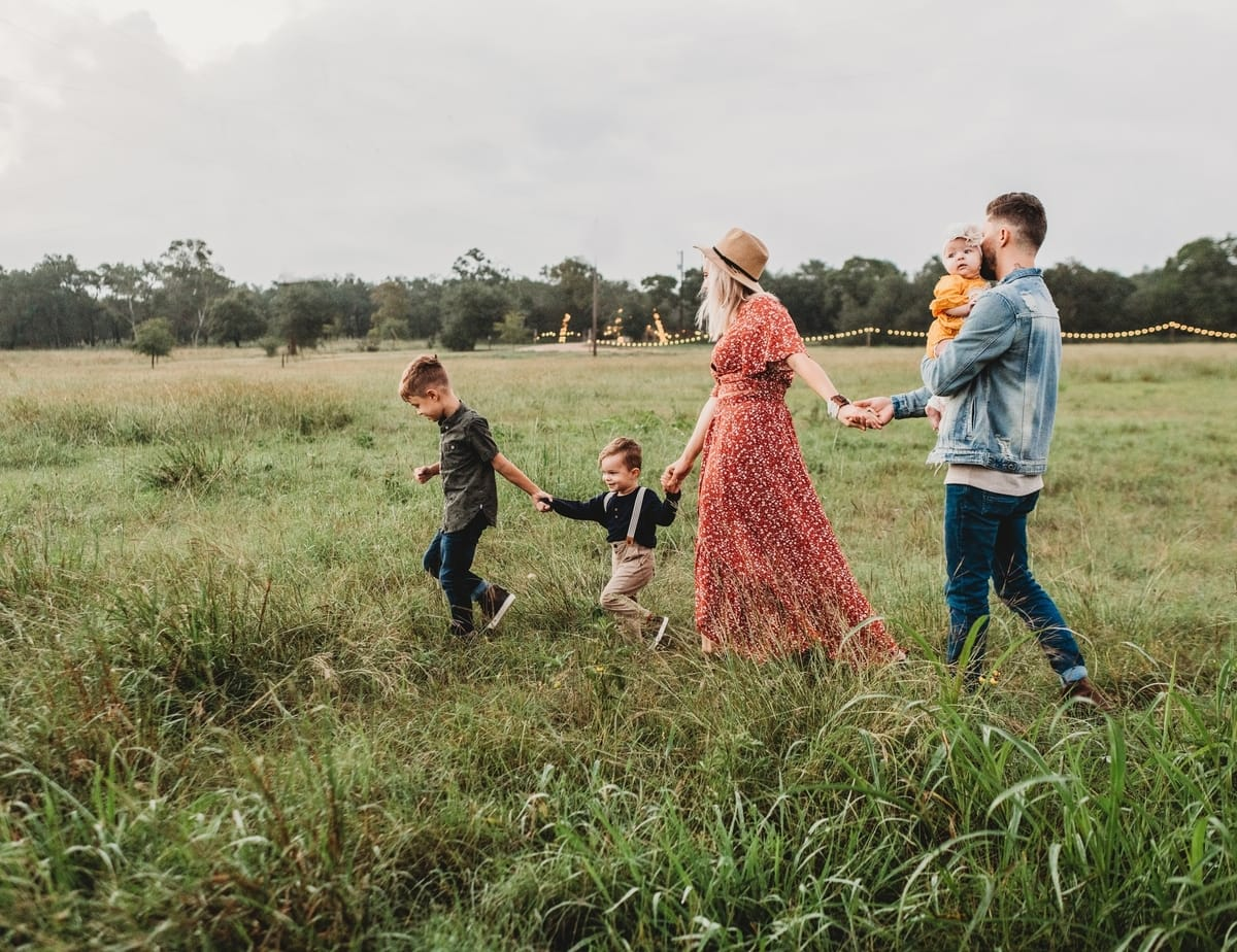 A family holding hands and walking in a field